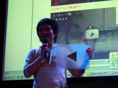 正面に構えて写真やビデオに映ると思わずクリックしたくなる「YouTubeの再生ボタン風板」。これも1つのAR?