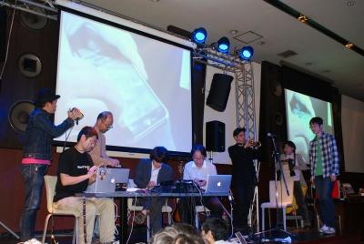 ザ・マネトロンズ+笠谷真也による演奏シーン。2つ前の写真との違いがほとんどない。ノリノリで演奏していても「ただiPhoneをいじっているオッサン集団」にしか見えないところが悲しい