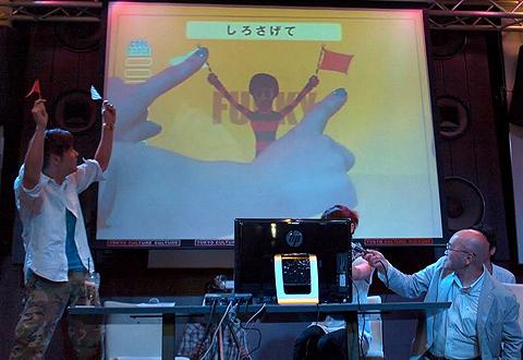 「SOUL FLAGS!」をデモする音無さん。スクリーンに映っているように、画面上の旗を指で上げ下げするのだが、どこかお間抜けな感じも。ちなみに、隣で吉川さんが実際の旗を持っているが、場を盛り上げるためでアプリとは直接関係ない
