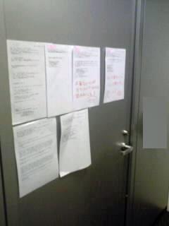 写真 JSOC入り口の扉にメールのプリントアウトを手書きの注意とともにぺたぺた貼って注意喚起