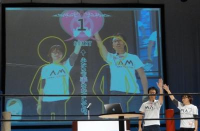 Kinectセンサを活用した「ミブリ・テブリ  -QUIZ kinect-」。○×のジェスチャーでクイズに答える。会場での実演は残念ながら失敗したが、福井とつないだオンラインデモも披露した。写真は2人対戦にも対応した新郎新婦用の結婚式バージョン