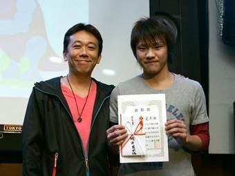 学生賞を受賞した栂井氏(右)とプレゼンターの日本マイクロソフト デベロッパー&プラットフォーム統括本部  アカデミックテクノロジー推進部部長の伊藤伸裕氏(左)