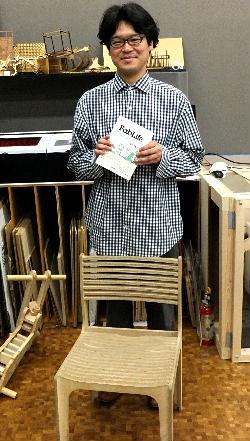 足下にあるのは、3Dスキャナで田中先生の体をスキャンし、体型にぴったり合うようにミリングマシンで制作した椅子。その脇にあるのは作りかけの子供用三輪車。後ろにはレーザーカッターとCNCミリングマシン