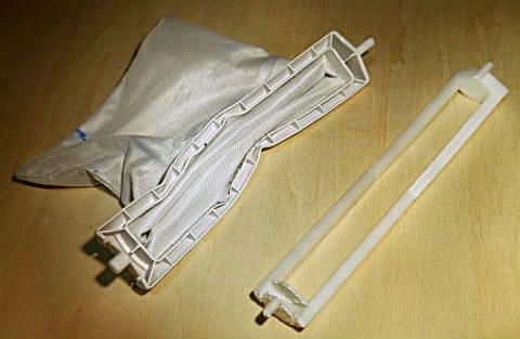 何かにぶつかってゆがんでしまった洗濯機のパーツ(左)。3Dプリンタで製作した自作の交換用パーツ(右) 製作・写真・田中浩也