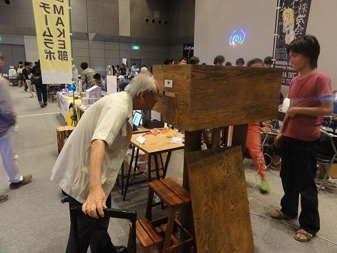 箱のプロジェクションマッピングをのぞき込む坂根先生(GOCCO)