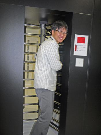 門を通り抜け、満面の笑みを浮かべる田中氏