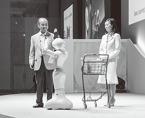 Pepperに商品を見せて質問する孫正義氏(「SoftBank World 2015」の基調講演にて)。