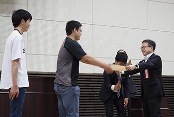 木更津工業高等専門学校の「Yone-labo」に経済産業大臣賞を手渡した世耕弘成経済産業大臣