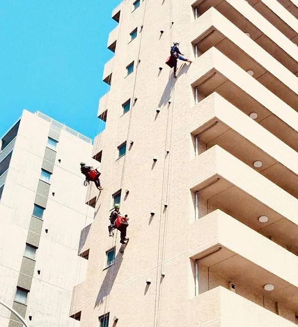 ロープアクセスでマンションの外壁を調査する様子
