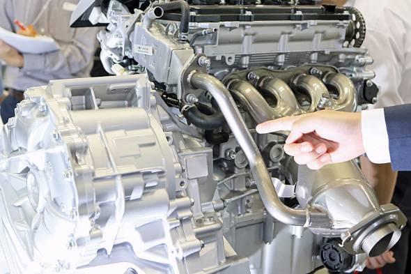 プリウス用の2ZR-FXE型1.8リットルエンジン。指さしているのが排気ガスを吸気管に導くパイプ。大量EGRを実現するため、水冷式の冷却器が取り付けられている