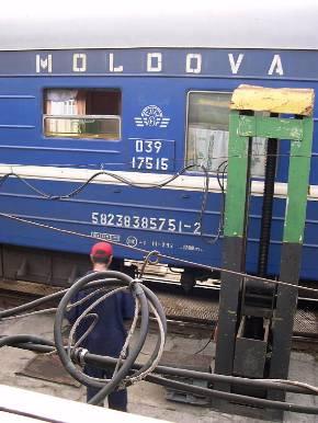 ロシアとルーマニアの国境、モルドバ駅の台車交換作業。ジャッキアップして台車を外す。車両の下に4本のレールが見える(出典:flickr、katesheets)