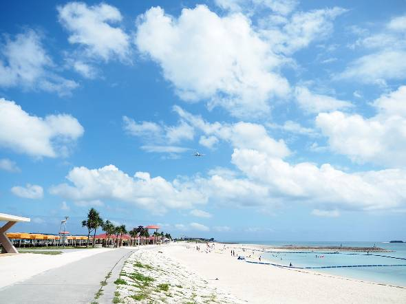 今年の会場となる「豊崎美らSUNビーチ」。那覇空港のすぐそばで、着陸態勢に入った飛行機が頭上を通過していく
