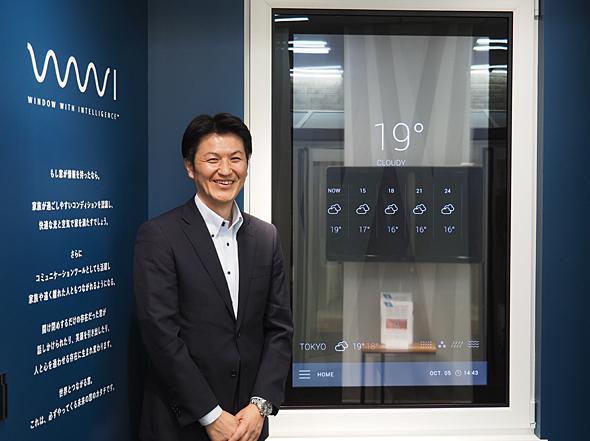 YKK AP 経営企画室 事業開発部長の東克紀氏。背景は、YKK AP ショールーム新宿に展示されている「Window with Intelligence」。屋外の気象情報も表示され、窓を眺めながら天気予報や、紫外線・花粉情報なども知ることができる