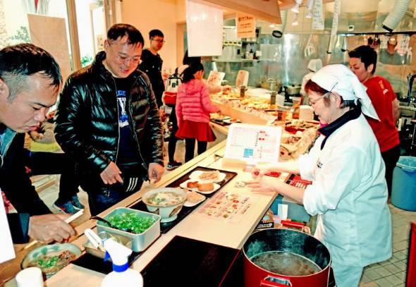 セルフで天ぷらや沖縄そばを注文する客たち=12日、北谷町・上間天ぷら沖縄そば店