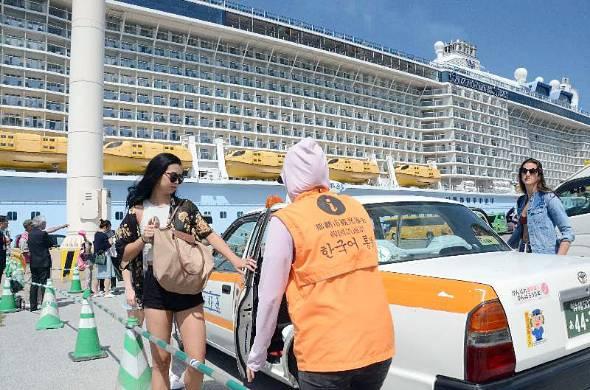 タクシーに乗り込むクルーズ船利用客=2日、那覇市那覇港国際コンテナターミナル