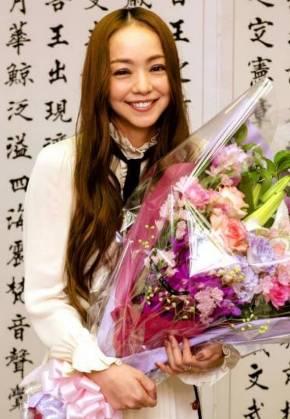 県職員から贈られた花束を手に笑顔を見せる安室奈美恵さん=23日、県庁