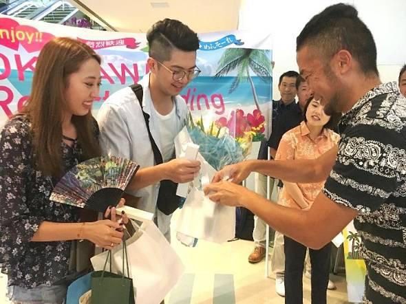 沖縄リゾートウェディング協会が開いた歓迎セレモニーで記念品などを受け取る台湾からのカップル(左の2人)=那覇空港