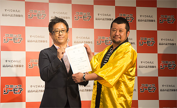 NTTソルマーレ取締役 コミック事業部長の荒谷篤志氏から1日宣伝部長に任命されたケンドーコバヤシさん