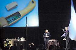 図2 米LiberatingTechnologies社の義手(人間の神経信号を受信し動かすことのできる腕と手)を紹介する、TI社社長兼CEOのRichardTempleton氏(右)