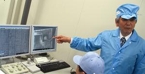 写真3 電子顕微鏡を使ったチップ分析について説明する佐藤信夫氏