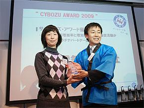 表彰するのはもちろん、ハッピ姿のサイボウズ青野社長。写真はプラチナパートナーとして優秀賞を受賞したNECの担当者