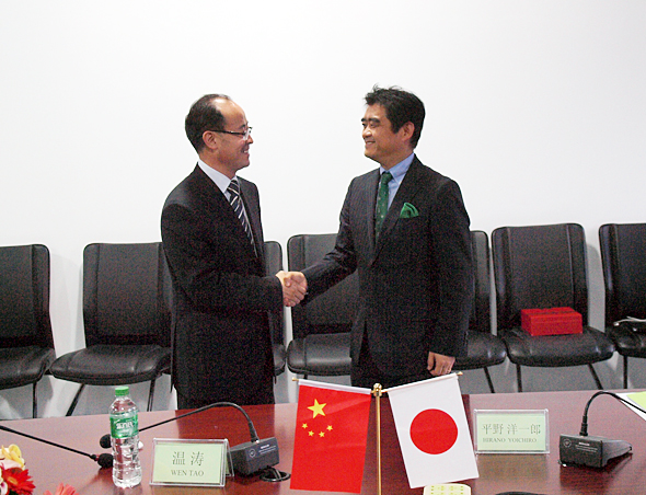 大連市内で行われた契約調印式で固く握手をする大連東軟信息学院の温涛学院長(左)とインフォテリアの平野洋一郎社長