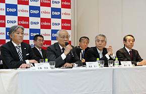 共同記者会見に臨む両社首脳。左から、大日本印刷の北島元治常務取締役、高波光一代表取締役副社長、日本ユニシスの黒川茂代表取締役社長、角泰志代表取締役専務執行役員