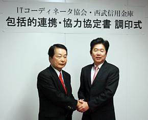 12月6日に開かれた調印式で握手するITコーディネータ協会 会長の播磨崇氏(左)と西武信用金庫 理事長の落合寛司氏