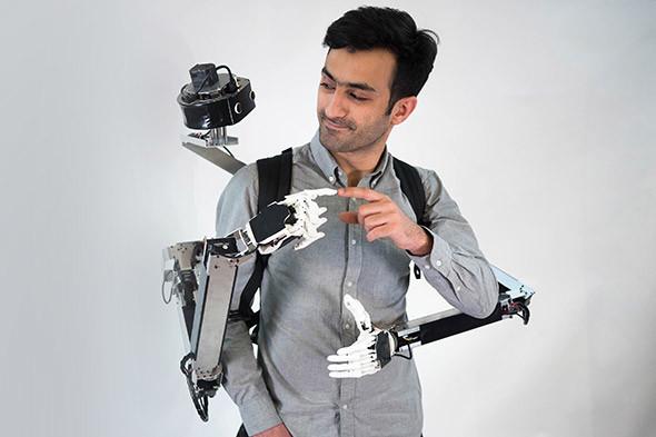 図1 「遠隔操作ロボット二人羽織」こと「Fusion」を装着した開発者のヤメン・サライジ慶應大学特任講師