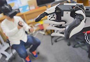 図3 左:Fusionの操作をしているサライジ氏 右:ロボットハンドで自分を指さす
