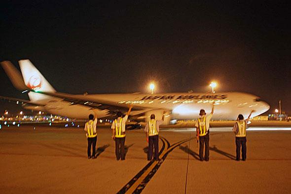 22時50分に再び成田に向けて出発する折り返しの724便を見送るスタッフたち