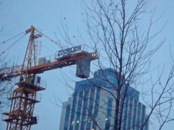 開発が進む青島市街地のビル建築現場に立つZoomlionの建機