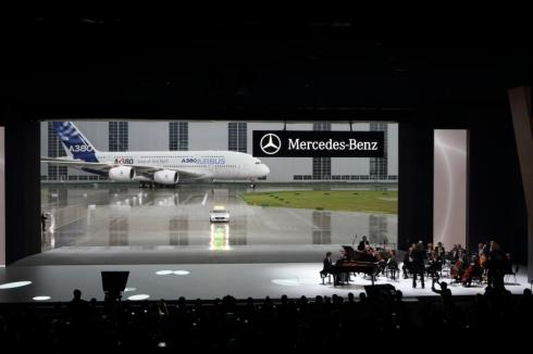 スクリーンの背後の扉が開くと、巨大な「A380」と「SLS AMG」が