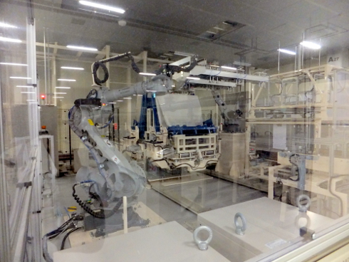 巨大アームロボットが自動台車からガラス基板をラインに乗せていく