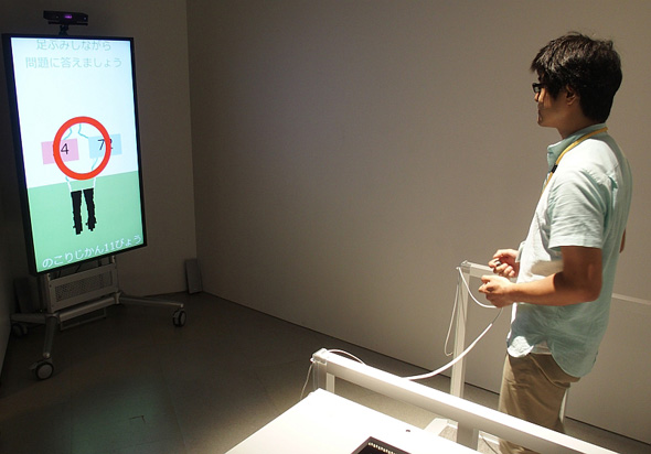 認知機能計測のデモンストレーションの様子。ディスプレイの上には足踏みしている姿を撮影する「Kinect」が(クリックで拡大)