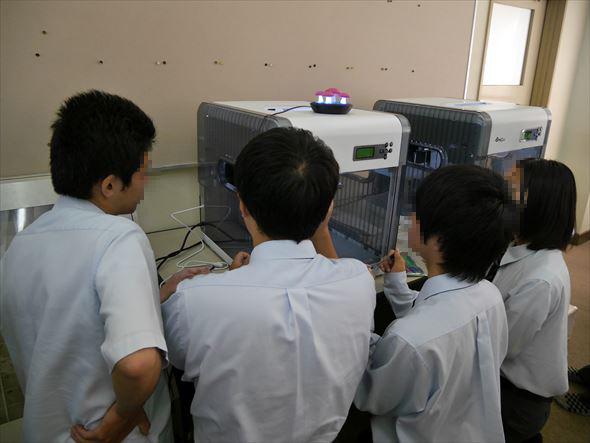 出力中の3Dプリンタに目がくぎ付けの生徒たち。「意外と時間かかる!」という感想が多かった