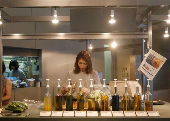 オープンキッチンの様子。並んでいるボトルはオリジナルドレッシングを作るためのビネガー