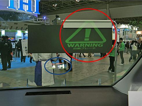 新開発の合わせガラス用中間膜にHUDを投影した様子。右上の赤丸で囲んだ緑の警告表示は中間膜の発光によるもの。左下にある青丸で囲だ表示は従来のHUD。表示サイズの違いが良く分かる