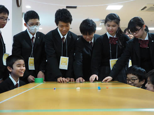 真剣にノック式ボールペンのボタンを押す生徒たち
