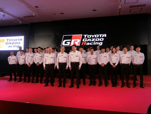 トヨタ自動車の嵯峨宏英氏(左)、同社 専務役員の伊勢清貴氏(中央)、Toyota Motorsportの佐藤俊男氏(右)。その後ろには、トヨタ自動車の2016年のモータースポーツ活動でハンドルを握るドライバー達が並ぶ