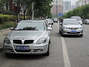 駐車中の華晨汽車「中華BS4」の脇を通り過ぎてゆく逸動