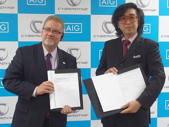 業務提携契約書に調印したAIGジャパンのロバート・ノディン氏(左)とサイバーダインの山海嘉之氏(右)