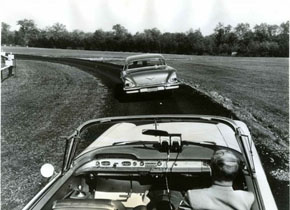 1950年代にGMとRCA(Radio Corporation of America)が実施した高速道路向けの自動運転のテスト。道路に埋設したスチールケーブルを車両に装着した磁石でトレースして走行したという。左側の運転席は無人でステアリングホイールも外されている