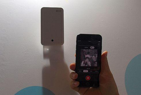 組み込みAIを搭載した小型IoTカメラ。左上にあるのが組み込みAIを搭載した小型IoTカメラ。スマートフォンの画面には、撮影データをリアルタイムで分析しており、認識した人やモノは赤い枠で示されている(クリックで拡大)