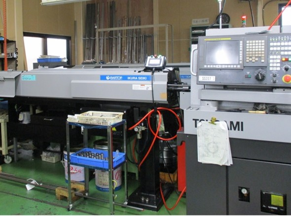 図7 「CNC自動旋盤」(右)と材料を送り出す「バーフィーダー」(左)