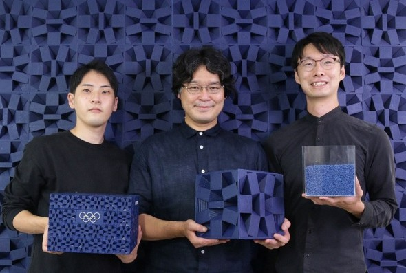 表彰台のベースとなったキューブを手にする田中浩也氏(中央)ら