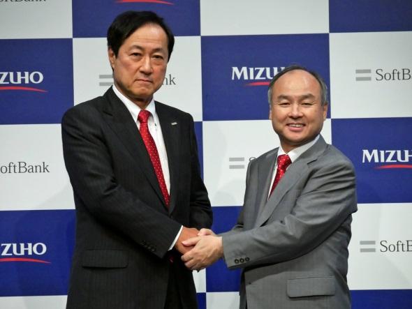 発表会で握手を交わす持株会社の首脳