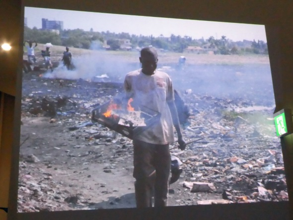 燃えるPCを持ちウィーンズCEOに近づくガーナの人