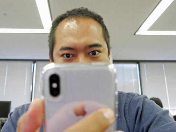 目を開けてiPhone Xを注視する筆者