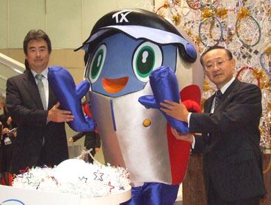 インテルの吉田社長(左)とTXの高橋社長。中央はTXマスコットの「スピーフィ」君